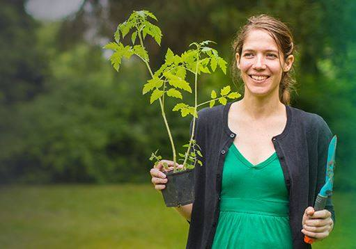 Danielle holding a tomato plant seedling for 1001 Belges tv episode.